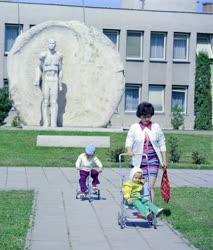 Életkép - Járókelők egy siklósi emlékmű előtt